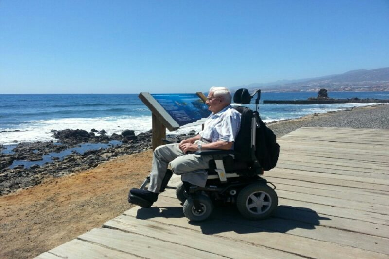 Reisburo vakantie en zorg man in rolstoel aan zee