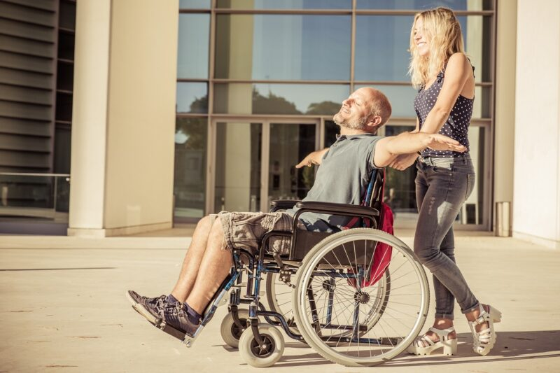 Reisburo Vakantie & Zorg vrouw duwt rolstoel man